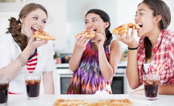 Adolescentes comiendo pizza